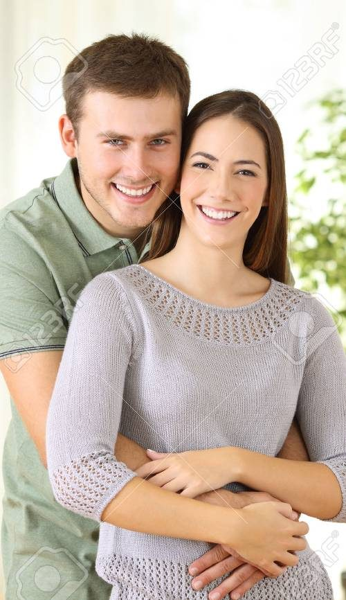 88148189-portrait-of-a-proud-homeowners-posing-looking-at-you-standing-in-the-living-room-at-home