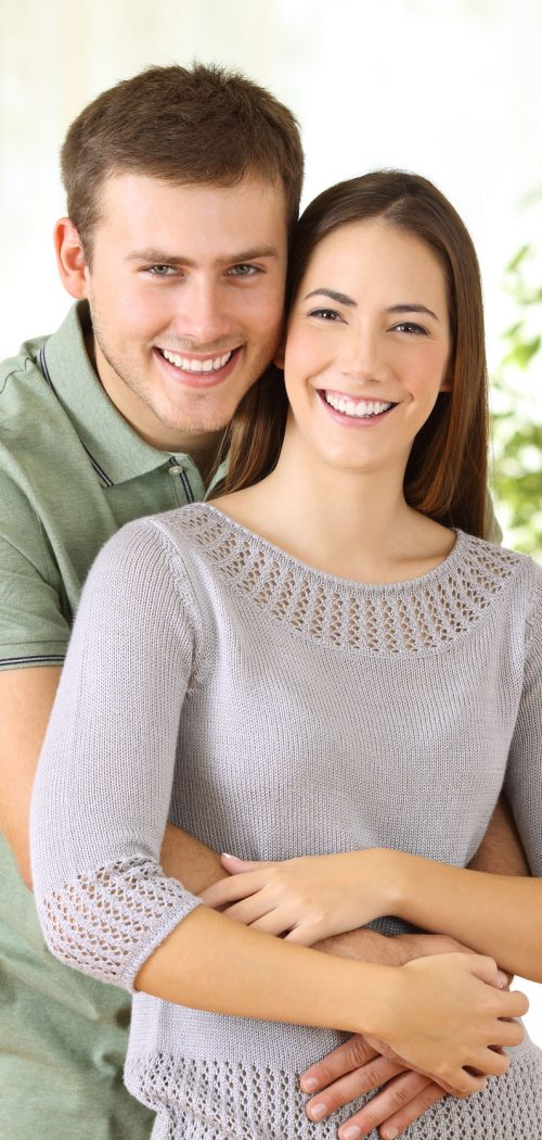 88148189 - portrait of a proud homeowners posing looking at you standing in the living room at home